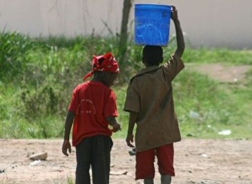 Two boys carry water home